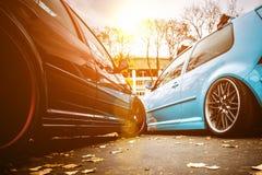 两修改了在棕色和浅兰的颜色的低汽车 有的姿态习惯汽车在街道上停放的伪造的优美的轮子在晴朗 免版税库存图片
