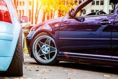 两修改了在紫色糖果和浅兰的颜色的低汽车 有的姿态习惯汽车在街道上停放的伪造的优美的轮子在 免版税图库摄影
