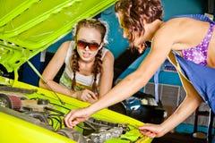 两修理汽车的女性汽车机械师 免版税库存照片