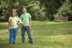 两儿童足球运动员 有球的男孩在绿草 库存图片