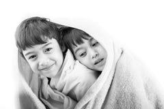 两兄弟姐妹在冷的冬天分享他们blanky 库存照片