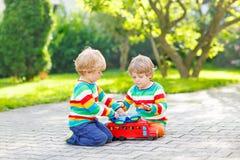 两兄弟姐妹,使用与红色木玩具的孩子男孩 库存图片