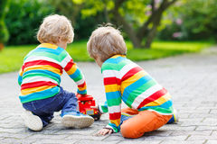 两兄弟姐妹,使用与红色校车的孩子男孩 免版税库存照片