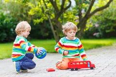 两兄弟姐妹,使用与红色校车的孩子男孩 免版税库存图片