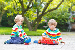 两兄弟姐妹,使用与红色校车的孩子男孩 免版税图库摄影
