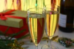 两充分的杯在圣诞节背景的香槟与杉树分支,与一个瓶香槟 免版税图库摄影