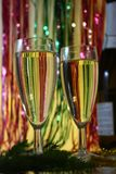 两充分的杯在圣诞节背景的香槟与杉树分支,与一个瓶香槟 免版税库存图片