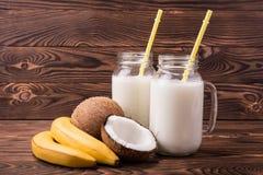 两充分透明金属螺盖玻璃瓶在黑褐色木背景的椰奶 水多的黄色香蕉和椰子在瓶子附近 库存照片