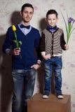 两先生们:年轻父亲和他的小逗人喜爱的儿子 人是举行 免版税库存照片