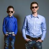 两先生们:年轻父亲和他的小逗人喜爱的儿子sunglasse的 库存照片
