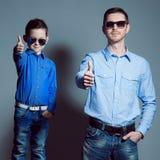 两先生们:年轻父亲和他的小逗人喜爱的儿子sunglasse的 免版税图库摄影
