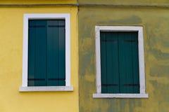 两关上了在黄色墙壁上的绿色窗口 库存图片