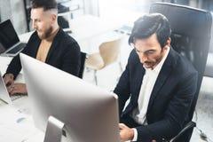 两典雅在台式计算机上的晴朗的办公室供以人员工作,当坐在木桌上时 被弄脏的背景,水平 库存图片