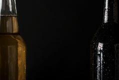 两冒汗,冷的瓶在黑背景的啤酒特写镜头 免版税库存图片