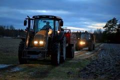 两农业拖拉机在冬天夜 免版税库存照片