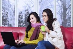 两冬天衣裳的女孩使用膝上型计算机 库存照片