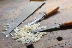 两凿子和一把锯在工作凳有一把木绑制钳的 免版税库存照片