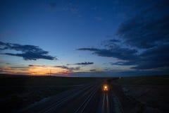 两列煤炭火车卷通过日落的怀俄明 免版税库存图片