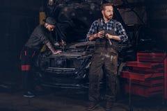 两制服的有胡子的汽车机械师,修理在车库的一辆残破的汽车 免版税图库摄影