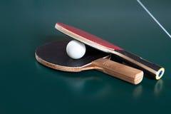 两副乒乓球球拍和一个球在一张蓝色桌上 r 库存图片