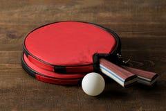 两副乒乓球球拍 台球球拍和一个球在一张棕色木桌上 体育比赛 库存照片