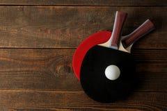两副乒乓球球拍 台球球拍和一个球在一张棕色木桌上 体育比赛 r 库存照片