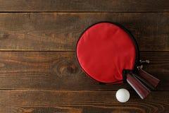 两副乒乓球球拍 台球球拍和一个球在一张棕色木桌上 体育比赛 r 免版税库存图片