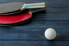 两副乒乓球球拍 台球球拍和一个球在一张蓝色木桌上 体育比赛 免版税库存图片