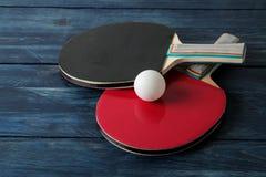 两副乒乓球球拍 台球球拍和一个球在一张蓝色木桌上 体育比赛 免版税图库摄影