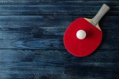 两副乒乓球球拍 台球球拍和一个球在一张蓝色木桌上 体育比赛 r 免版税库存照片