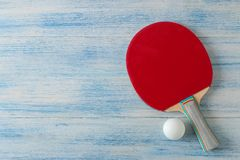 两副乒乓球球拍 台球球拍和一个球在一张蓝色木桌上 体育比赛 r 库存照片