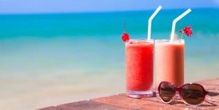 两副鸡尾酒和太阳镜的图片在桌上 免版税库存照片