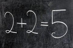 两加上在黑板的两均等五 免版税库存照片