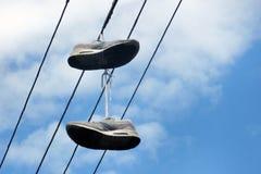 两双在电导线的老运动鞋吊 概念是时刻一个假期 免版税库存照片