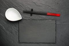 两双筷子和白色碗在黑石背景 库存图片