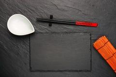 两双筷子和白色碗在黑石背景 免版税图库摄影
