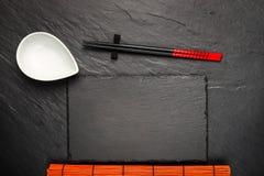两双筷子和白色碗在黑石背景 免版税库存照片