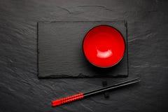 两双筷子和红色板材在黑石背景与copyspace 免版税库存照片