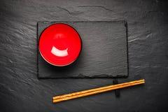 两双筷子和红色板材在黑石背景与copyspace 免版税库存图片