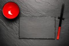 两双筷子和红色板材在黑石背景与copyspace 库存照片