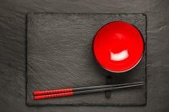 两双筷子和红色板材在黑石背景与copyspace 免版税图库摄影