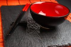 两双筷子和红色板材在黑石背景 库存照片
