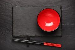 两双筷子和红色板材在黑石背景 免版税库存照片