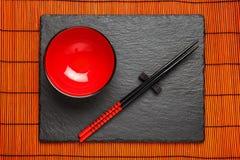 两双筷子和红色板材在黑石背景 图库摄影