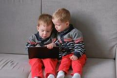 两双胞胎互相拿走` s片剂坐沙发 孩子在片剂的戏剧比赛 图库摄影