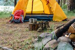 两双金属杯子和鞋子在火附近的森林 库存图片