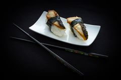 两双nigiri鳗鱼寿司和筷子在黑色 免版税库存照片