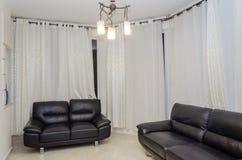 两反对白色帷幕的黑长沙发在客舱公寓 库存照片
