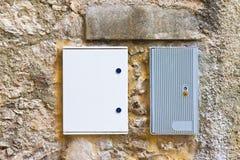 两反对石头和砖wa的电子塑料接线盒 图库摄影