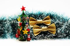 两反对绿色圣诞树闪亮金属片和一块微型记忆玻璃背景的欢乐金蝴蝶蝶形领结  库存照片